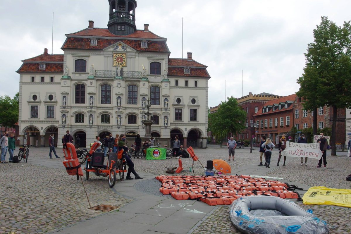 Kundgebung am Marktplatz mit Rettungswesten und Bannern