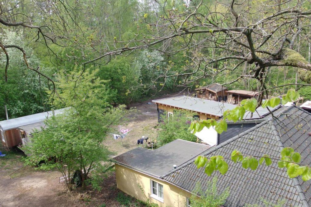 Haus mit Bauwagen, von einem Baum aus aufgenommen