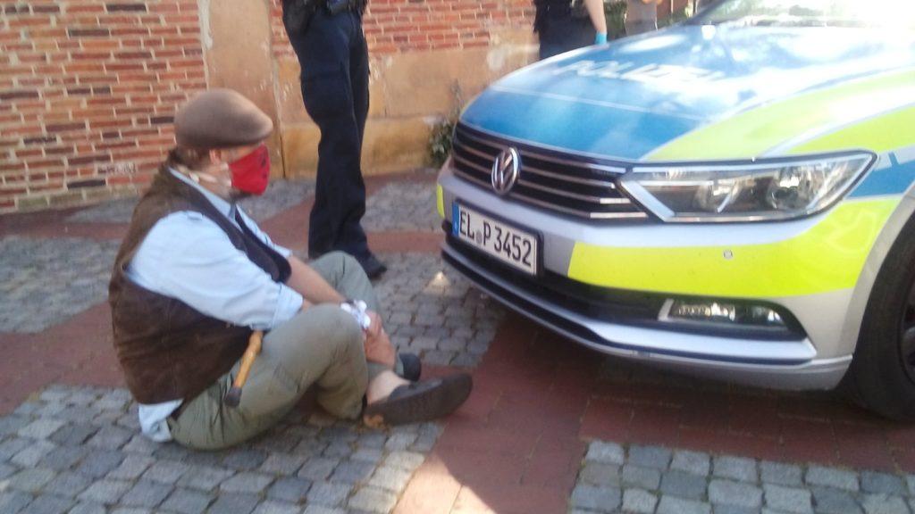 Ein Aktivist sitzt vor einem Polizeiauto