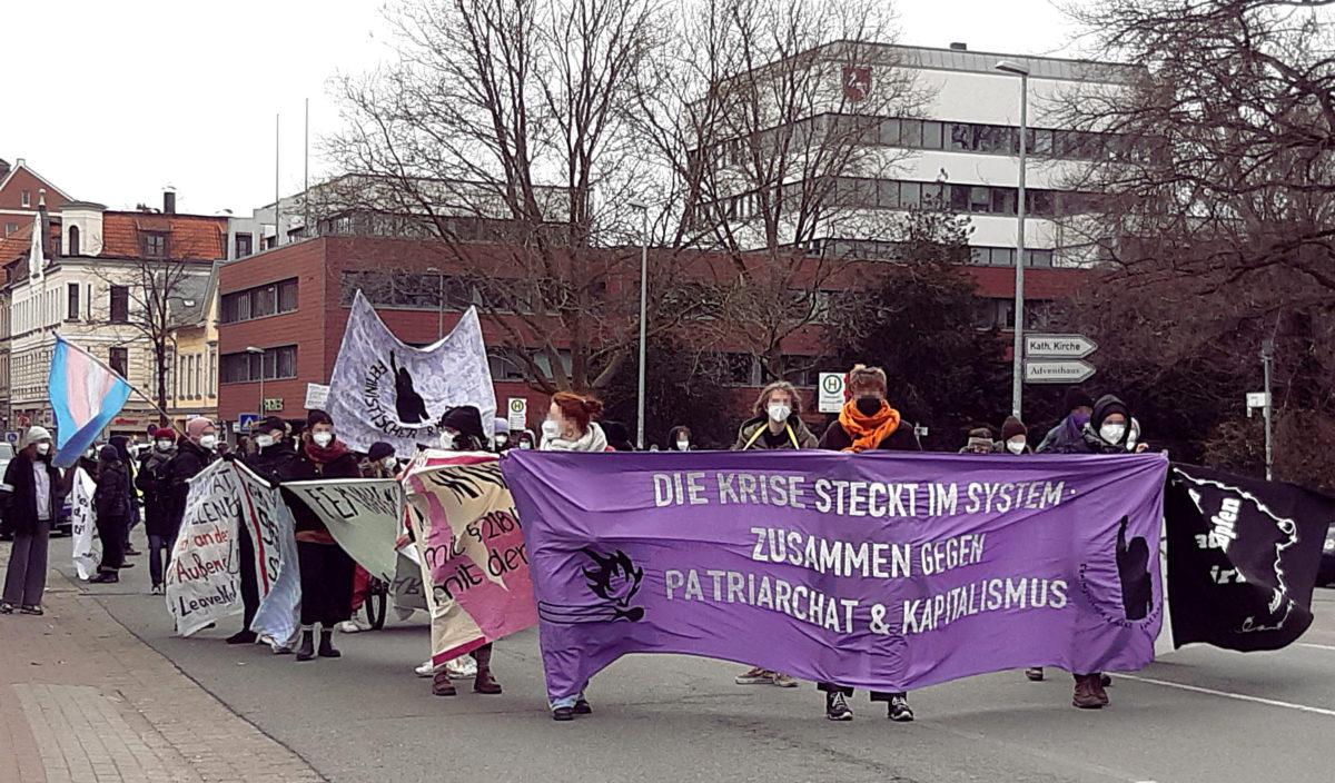 """7.3.2021 Feministische Demo in Lüneburg mit violettem Frontbanner: """" Die Krise steckt im System - Zusammen gegen Patriachat und Kapitalismus"""