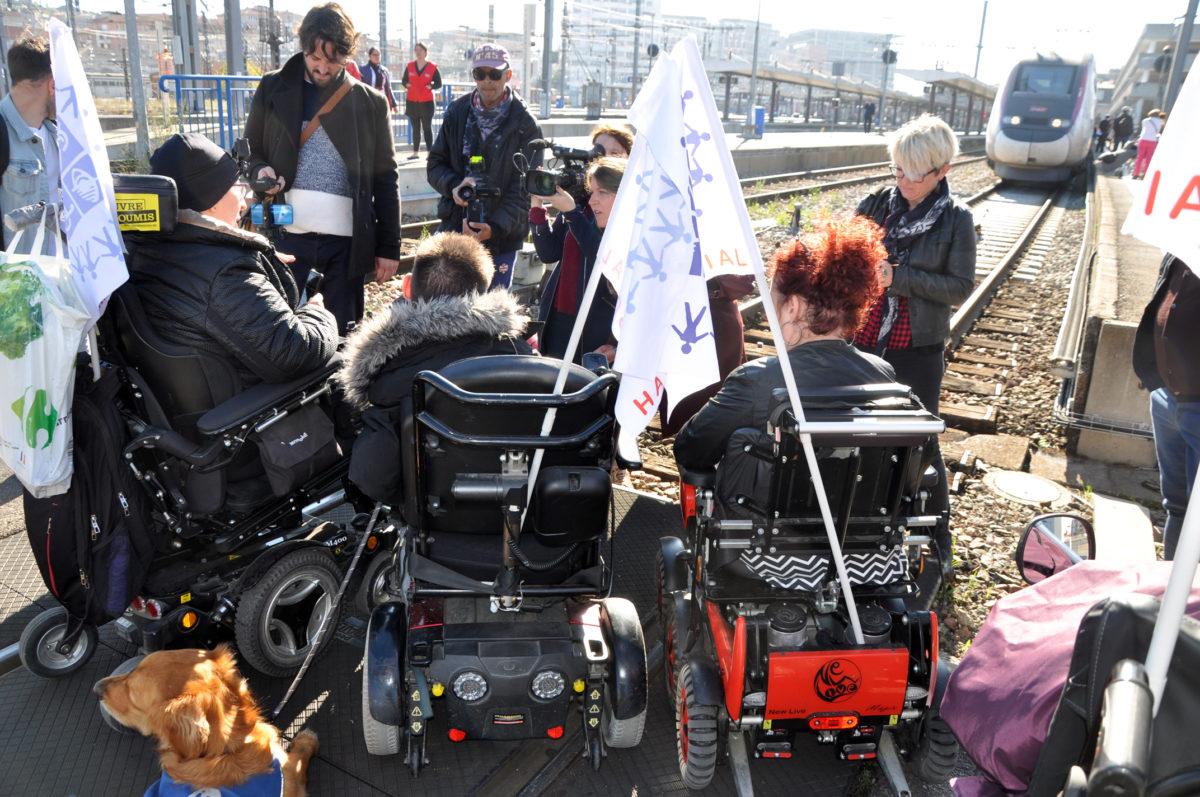 3 Personen im E-Rollstuhl sind auf Bahngleise von hinten zu sehen. Die presse filmt. Im Hintergrund ist ein stehender TGV Zug zu sehen.