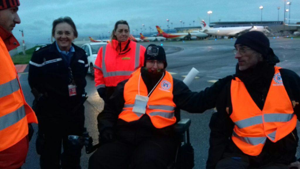 Rollstuhlfahrende Menschen und Fußgänger*innen auf dem Rollfeld vom Flughafen in Toulouse, im hintergrund sind Flugzeuge zu sehen