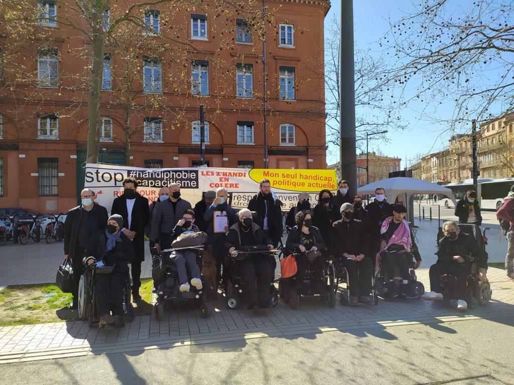 Aktivistinnen mit Banner und Forderung nach Barrierefreiheit vor ihrem Prozess.