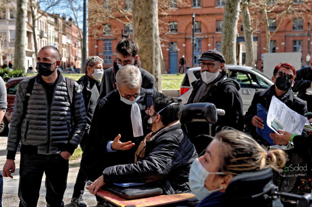 Anwalt in Robe spricht mit einer der Angeklagten im Rollstuhl vor dem Gerichtsgebäude in Toulouse