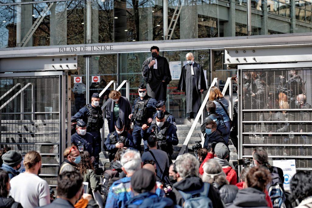 Gerichtsgebäude mit Stuffen, oben sthehen zwei Anwälte in schwarzer Robe. Vor der Treppe viele Menschen, auf der Treppe viel Polizei