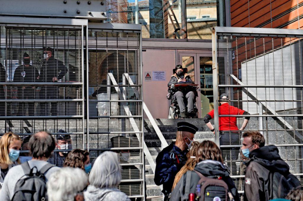 """Rollstuhlfahrerin steht oben, vor Ihr eine Treppe. unten: menschen und Polizei. Oben Links am Gebäude: """"Palias de justice"""""""