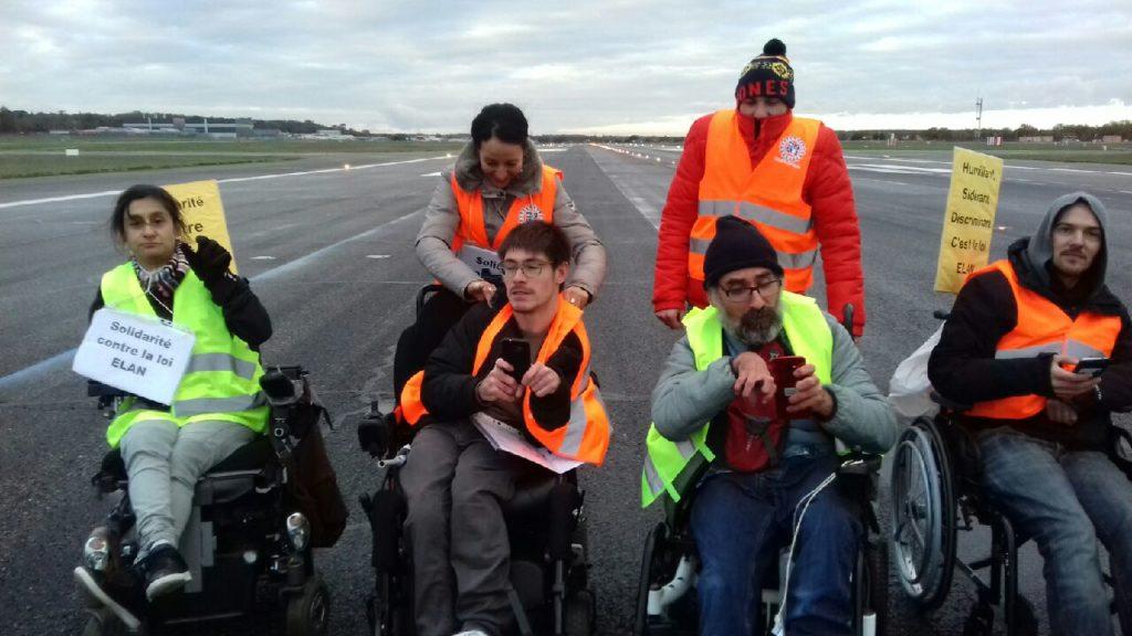 Menschen mit und ohne Rollstuhl auf dem Rollfeld vom Flughafen. Sie tragen Warnwesten